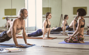 A man and woman demonstrate upward dog for yoga teacher training instructor